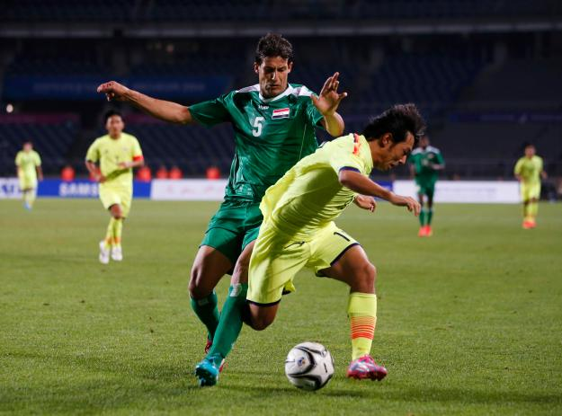 Iraq's Suad Natiq Naji fights for the ball with Japan's Shoya Nakajima during their men's soccer qualifier match at Goyang Stadium in Goyang, for the 17th Asian Games in Incheon