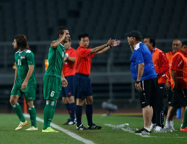 Iraq's Al Tameemi Ali Adnan Kahim celebrates with their head coach Al Azzawi Hakeem Shakir Flayyih after scoring a goal against Japan during their men's soccer qualifier match for the 17th Asian Games at Goyang Stadium in Goyang