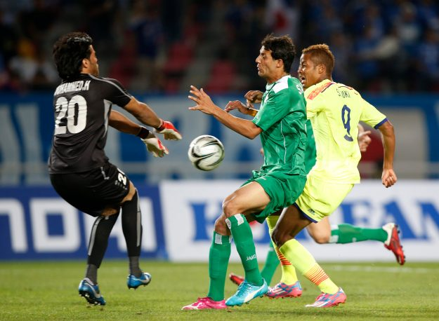 Iraq's goalkeeper Hameed Farhan runs to intercept the ball during their men's soccer qualifier match against Japan for the 17th Asian Games at Goyang Stadium in Goyang