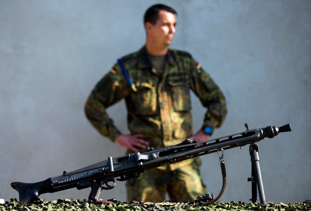 A soldier stands behind a MG3 automatic weapon that is part of a German military aid shipment for Kurdish forces in Northern Iraq at a storage facility of the Bundeswehr armed forces in Waren