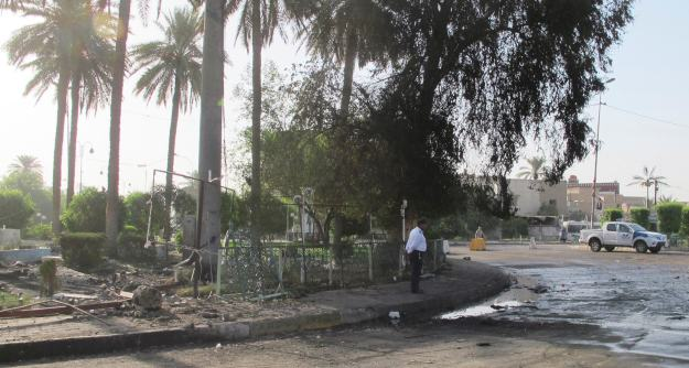 Traffic policeman stands at the site of a bomb attack in Baghdad's Kadhimiya district