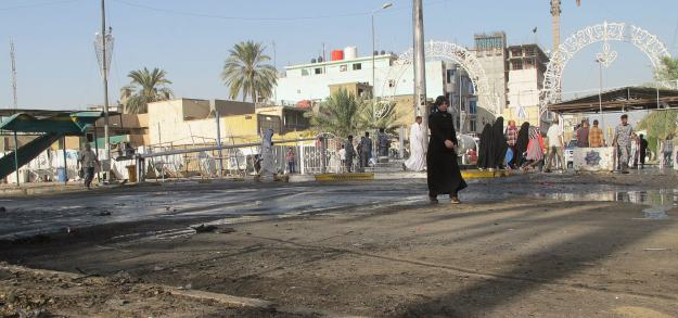 Woman walks past the site of a bomb attack in Baghdad's Kadhimiya district