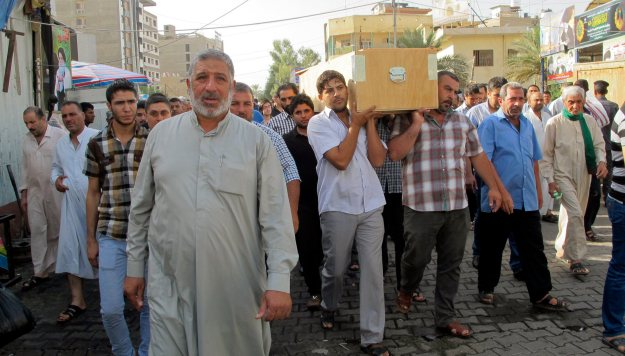 Mourners carry the coffin of their relative, who was killed in a car bomb attack in Baghdad's Kadhimiya district