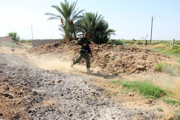 Shi'ite fighter from Saraya al-Salam runs during clashes with Islamic State militants in Jurf al-Sakhar