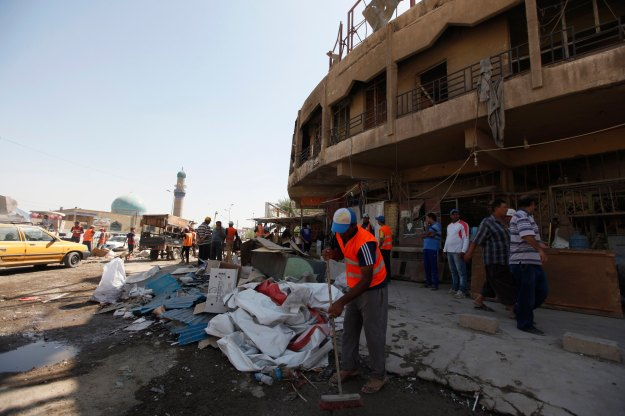 Municipal workers clean the site of a car bomb attack in Baghdad's Ur district