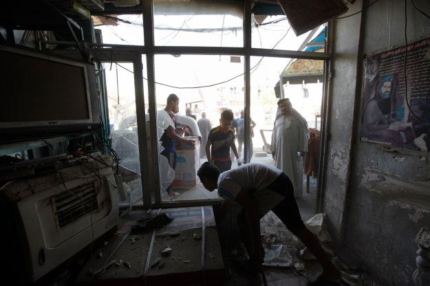 People inspect the site of a car bomb attack in Baghdad's Ur district