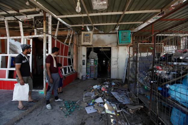People look at the site of a car bomb attack in Baghdad's Ur district
