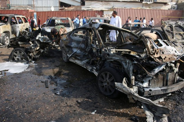 People inspect the site of a car bomb attack in Basra, southeast of Baghdad