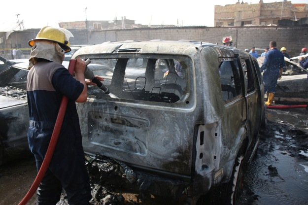 A firefighter hoses down a vehicle after a car bomb attack in Basra, southeast of Baghdad