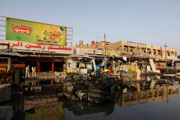 People gather at the site of a car bomb attack in Zaa'franiya district in Baghdad