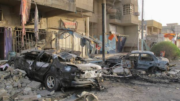 Damaged vehicles are seen at the site of a car bomb attack in Baghdad