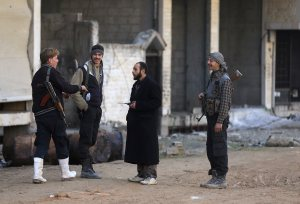 Rebel fighters from the Free Syrian Army's Al Rahman legion chat along a street in Jobar