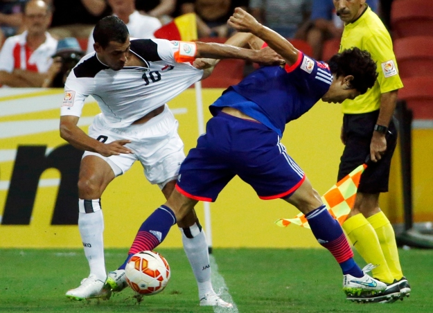 Iraq's Younus Mahmood fights for the ball against Japan's Masato Morishige during their Asian Cup Group D soccer match at the Brisbane Stadium in Brisbane