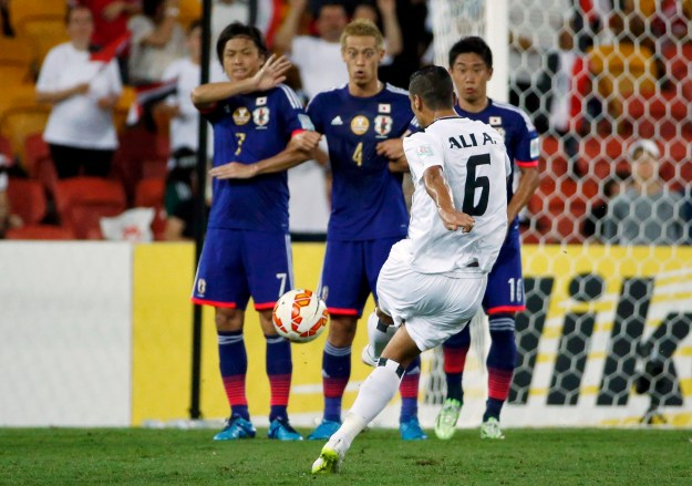 Iraq's Ali Adnan Kadhim takes a free kick toward the Japan defensive wall of (L to R) Yasuhito Endo, Keisuke Honda and Shinji Kagawa during their Asian Cup Group D soccer match at the Brisbane Stadium in Brisbane