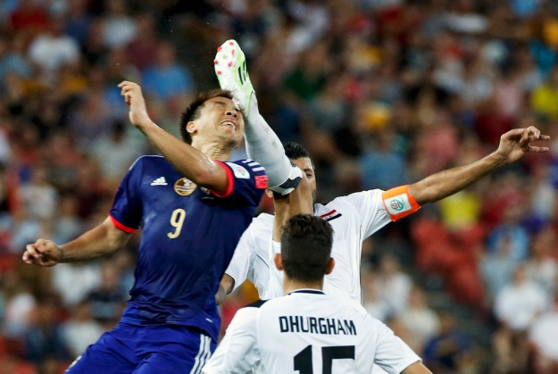 Japan's Shinji Okazaki is kicked on the back of the head by Iraq's Salam Shakir as they go for the high ball during their Asian Cup Group D soccer match at the Brisbane Stadium in Brisbane