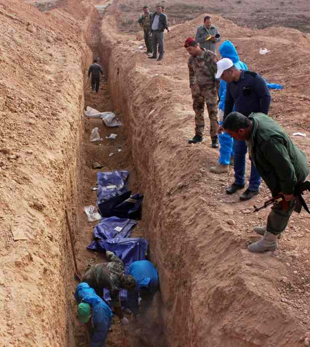 Men excavate remains from a mass grave on the outskirts of Saadia