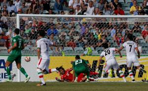 Iran's Sardar Azmoun scores a goal past Iraq's goalkeeper Jalal Hassan Hachim during their Asian Cup quarter-final soccer match at the Canberra stadium in Canberra