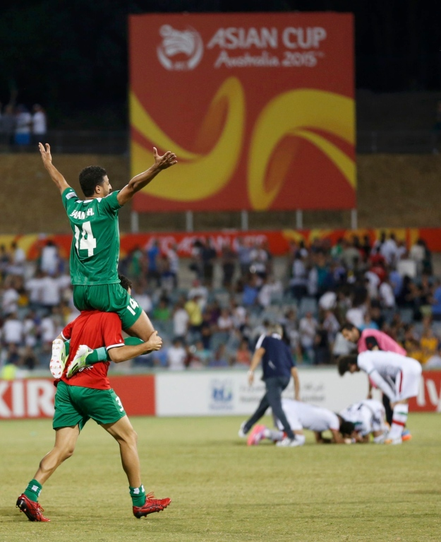 Iraq's Salam Shakir is lifted by Ali Bahjat Fadhil as he celebrates scoring the match winning penalty after the penalty shoot out against Iran in their Asian Cup quarter-final soccer match at the Canberra stadium in Canberra