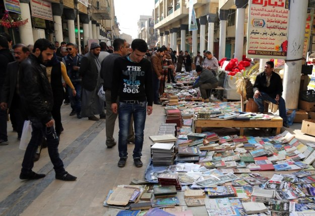 In this Friday, Jan. 23, 2015 photo, Iraqis look at books on al-Mutanabi Street, home to the city's book market in central Baghdad.