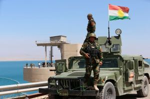 Peshmerga fighters stand on a vehicle with a Kurdish flag as they guard Mosul Dam in northern Iraq