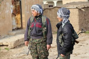 Kurdish fighters stand with their weapons between the towns of Rabia and Snuny