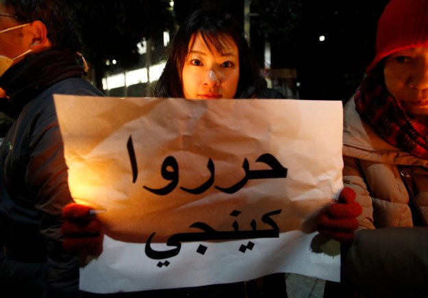 "Woman holding a placard reading ""Free Kenji"" during a vigil in front of the PM Abe's official residence in Tokyo"