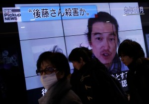 People walk past television screens displaying a news program about Japanese journalist Kenji Goto on a street in Tokyo