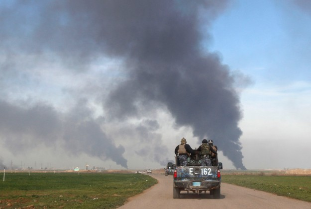 Vehicles of the Iraqi security forces patrol the road near the Khabbaz oilfield on the outskirts of Kirkuk
